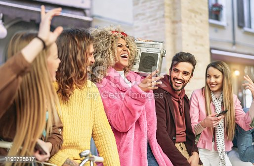 861023492 istock photo Group friends having fun listening music with vintage boombox - Happy young people making party in city outdoor  - Youth culture and millennial lifestyle concept 1192728617