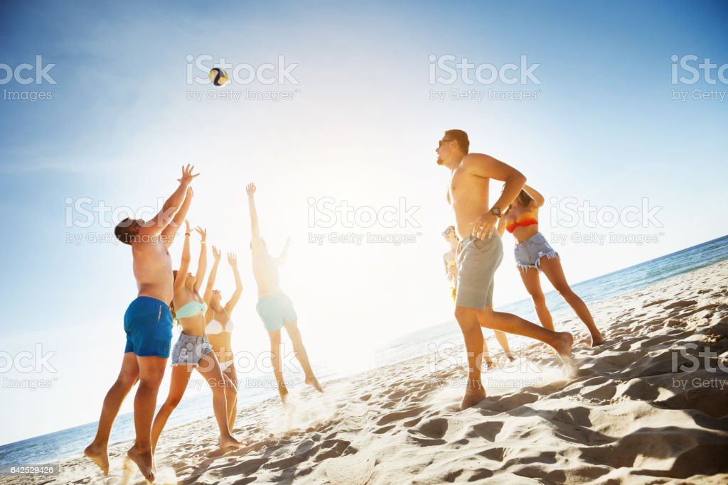 Group friends plays ball beach sea stock photo