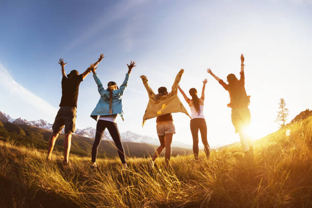 Group happy friends mountains sunset raised arms