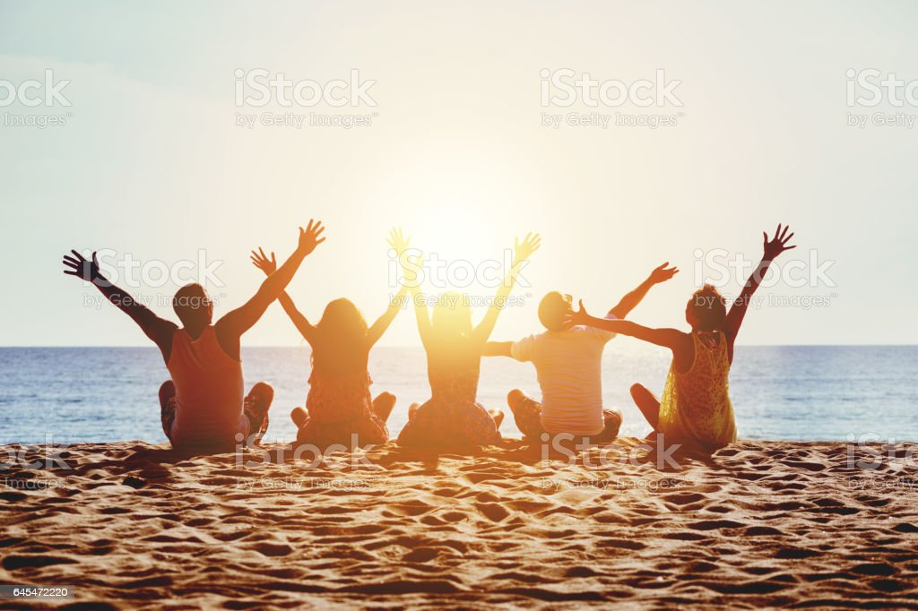 Group happy people beach sea sunset concept stock photo