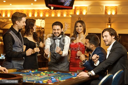 Group happy people make bets gambiling at the roulette table in the casino. Gambling in a casino.