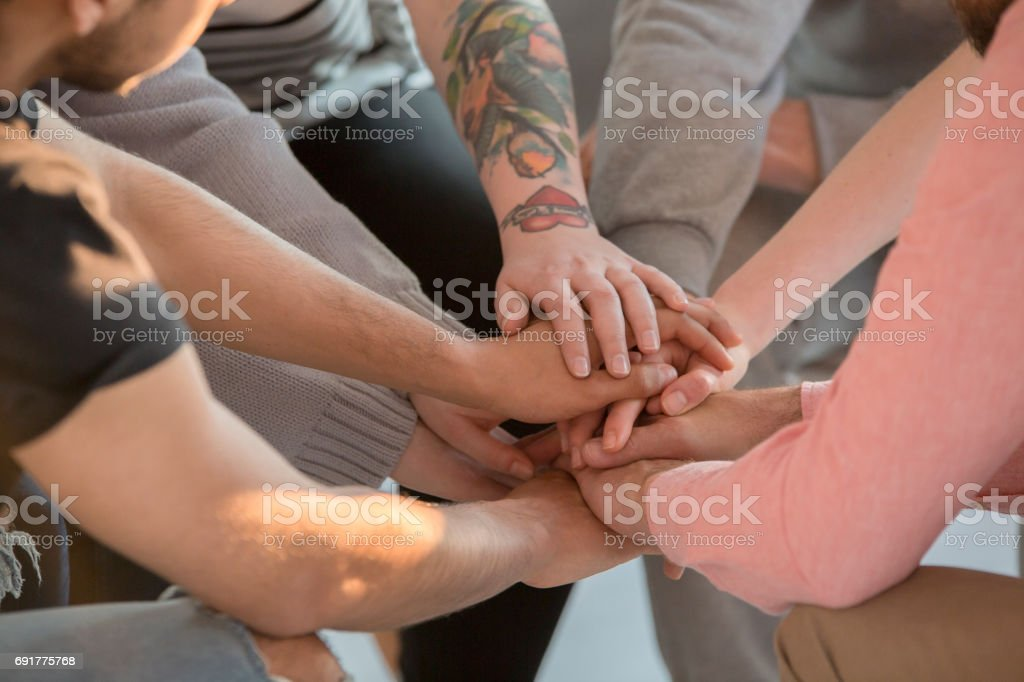 Group holding hands together stock photo