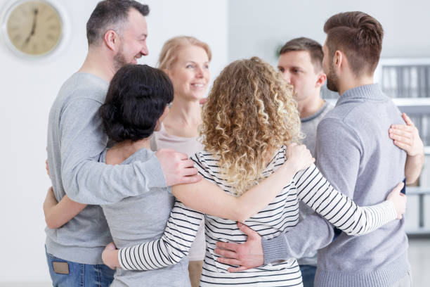 Group hug during therapy People having group hug during therapy in rehab drug rehab stock pictures, royalty-free photos & images