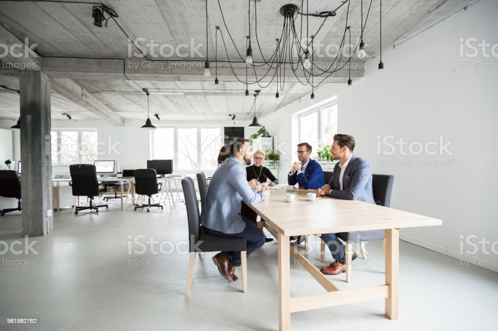 Group in modern office having a meeting Group in modern office having a brainstorming meeting. Business people discussing over new business project in office. Active Seniors Stock Photo
