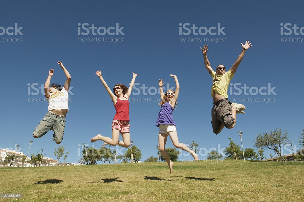 group jumping in the sunshine on a hill royalty free stockfoto