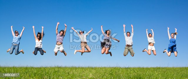 Group of friends jumping in meadow under blue sky. Panoramic format.