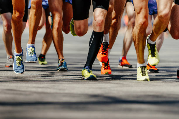 group legs runners athletes group legs runners athletes run on asphalt road marathon running stock pictures, royalty-free photos & images