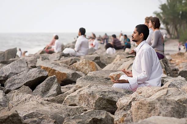 Group meditation on the beach. stock photo