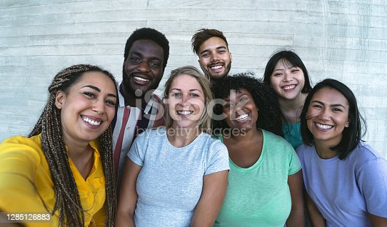Group multiracial friends having fun outdoor - Happy mixed race people taking selfie together - Youth millennial generation and multi ethnic teenagers lifestyle concept