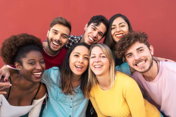 團體多種族人有樂趣戶外 - 快樂混合種族朋友分享時間在一起 - 青年千禧一代和多民族青少年的生活方式概念 - 紅色背景 - 年輕成年人 個照片及圖片檔