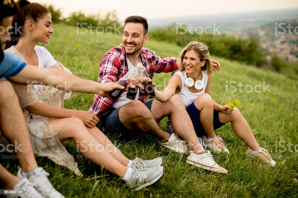 Group od young people drinking and having fun on a trip in nature on mountain royalty-free stock photo
