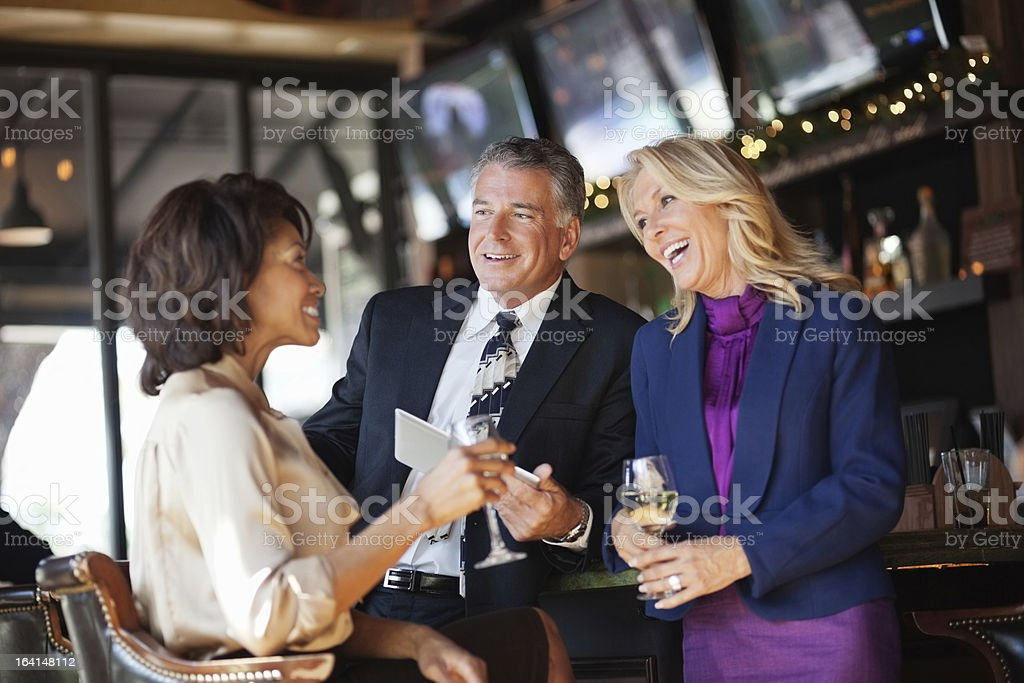 Group of 3 business people smiling & drinking in a bar royalty-free stock photo