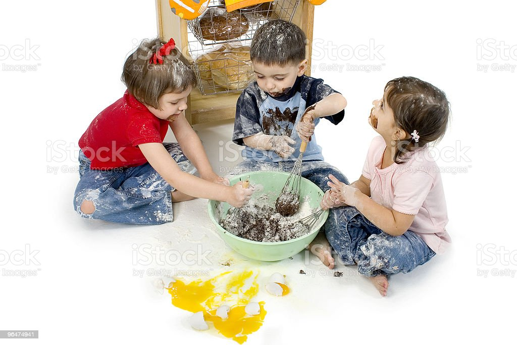 Group of 3 children trying to make a cake covered in flour royalty-free stock photo