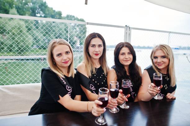 gruppe von 4 mädchen auf schwarz mit champagner gläser am junggesellinnenabschied. - outdoor braut duschen stock-fotos und bilder