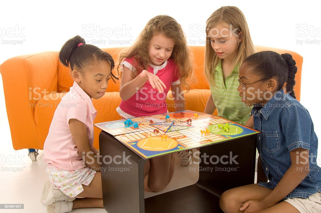 Group of 4 young children sat around playing board games stock photo