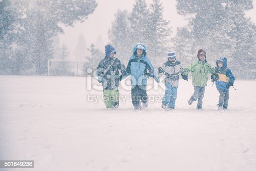 865399512istockphoto Group of 5 children run in a snowy storm 501849236
