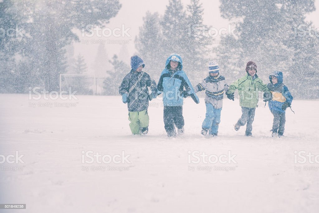 Group of 5 children run in a snowy storm stock photo