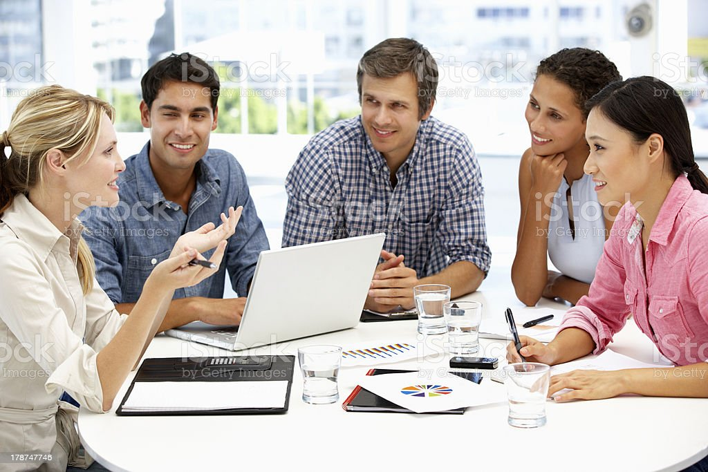 Group of 5 smiling people at a business meeting, one winking stock photo