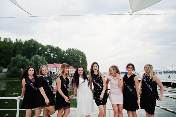 gruppe von 8 mädchen tragen auf schwarz und 2 bräute am junggesellinnenabschied - outdoor braut duschen stock-fotos und bilder