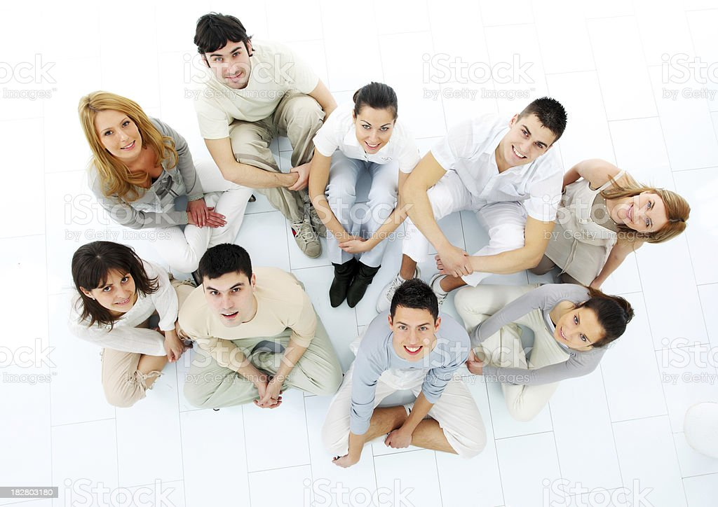 Group of a friends sitting on floor and looking up. royalty-free stock photo