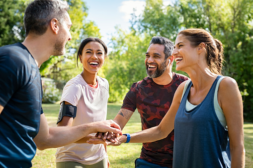 Laughing mature and multiethnic sports people putting hands together at park. Happy group of men and beautiful women smiling and stacking hands outdoor after fitness training. Multiethnic sweaty team cheering after intense training.