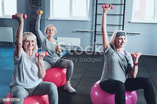 936573360 istock photo Group of active senior ladies training with dumbbells at gym 936573706