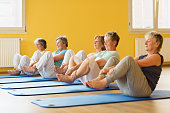 istock group of active senior women in yoga class exercising on mat 935993048