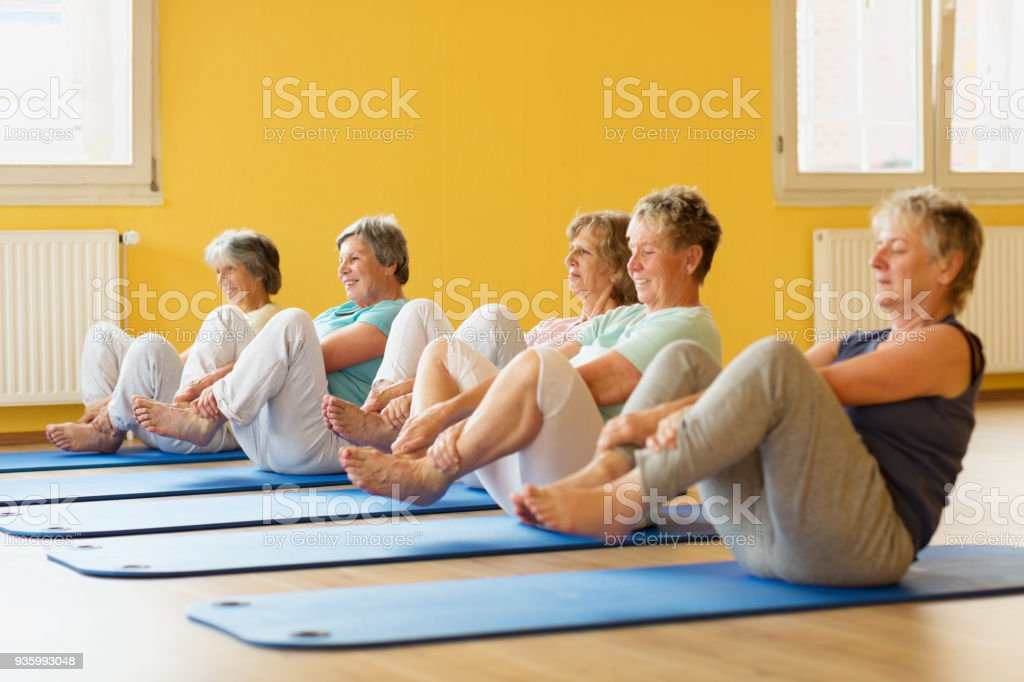 group of active senior women in yoga class exercising on mat stock photo