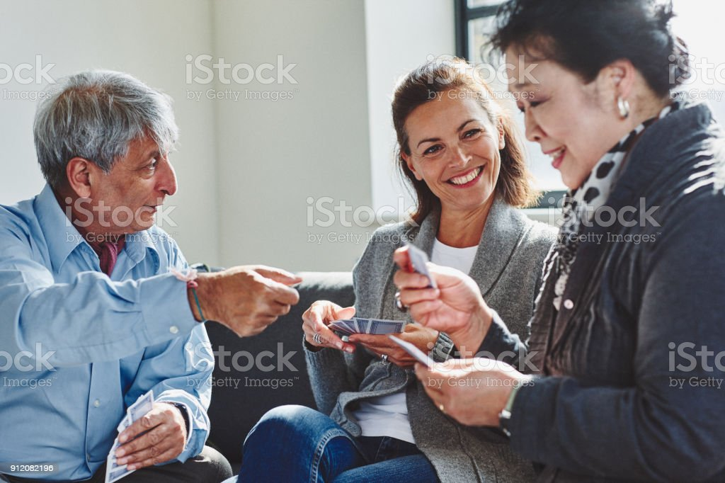 Group of active seniors enjoying game of cards at retirement home