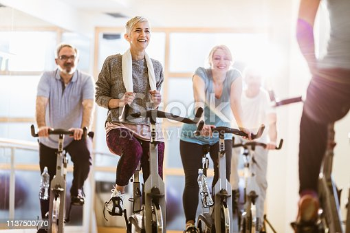 Happy mature athletes exercise on exercises bikes while having sports training with their coach. Focus is on woman with short hair.