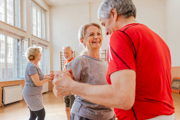 group of active seniors having fun dancing together - dance class stock photos and pictures