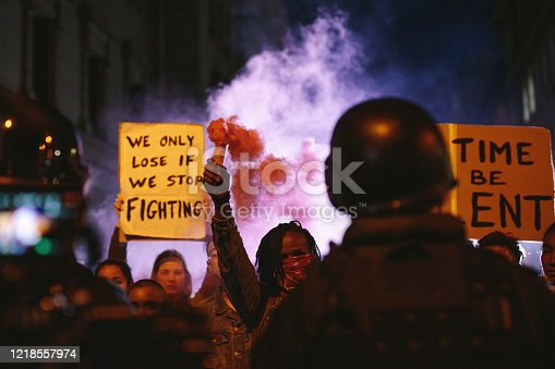 Group of activists protesting with smoke grenades at night. Group of men and women on anti-government protest.