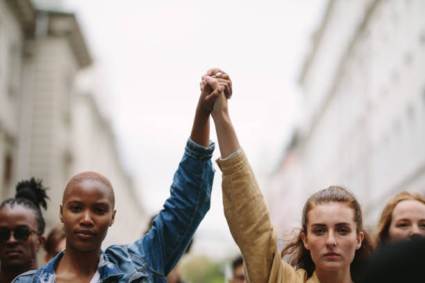 Group of activists with holding hands protesting Group of activists with holding hands protesting in the city. Rebellions doing demonstration on the street holding hands. unity stock pictures, royalty-free photos & images