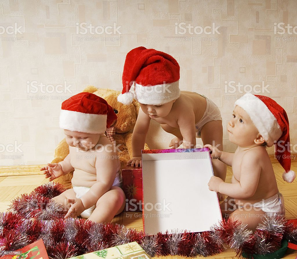 Group of adorable toddlers in Christmas hats packing presents royalty-free stock photo