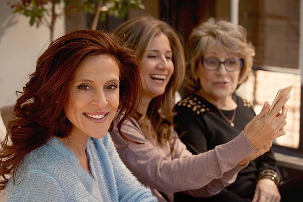 group of adult and senior women with phone - altes damenhaar stock-fotos und bilder
