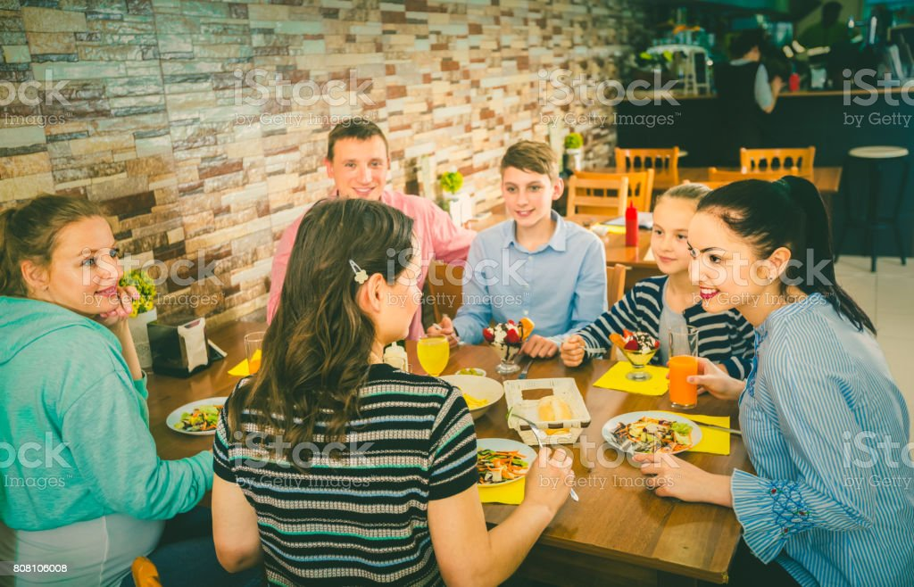 Group of adults and teenagers spending time in  cafe stock photo