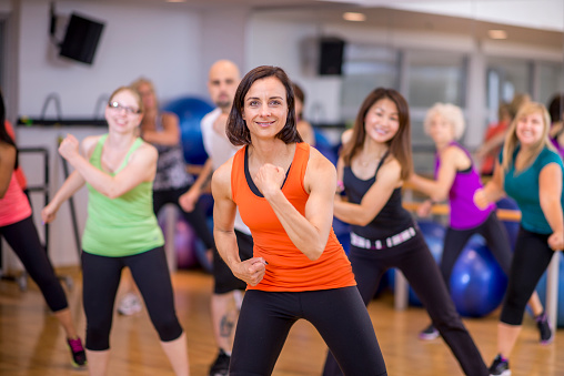 A multi-ethnic group of adults are taking a dance fitness class together at the the gym.
