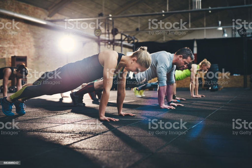 Group of adults doing push up exercises stock photo