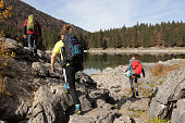 Group of Adults Hiking By a Lake in Julian Alps in Italy.