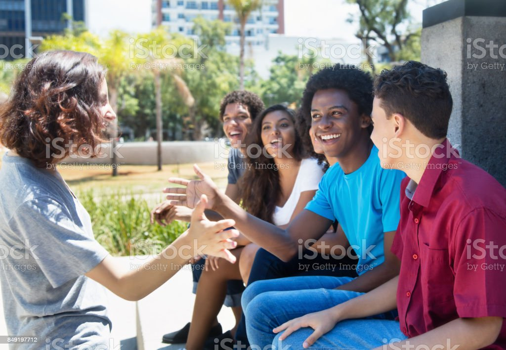 Group of african american and latin people welcoming a caucasian girl stock photo