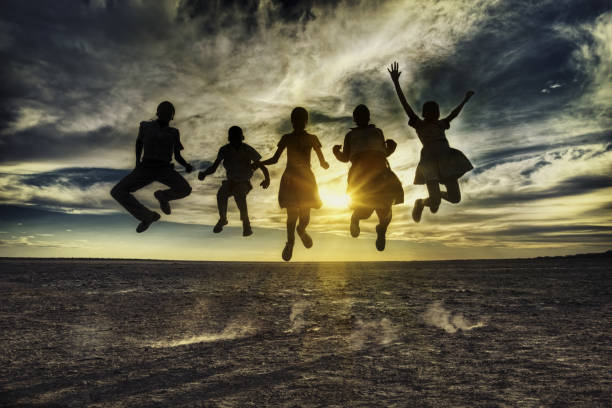 Group of african kids jumping in the sunset