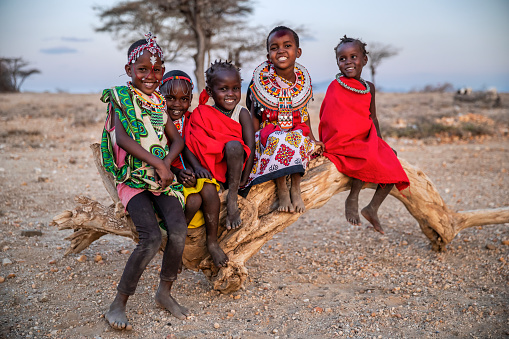 Group of happy African little children from Samburu tribe sitting on tree trunk, Kenya, Africa. Samburu tribe is north-central Kenya, and they are related to  the Maasai.