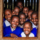 Group of African school children inside classroom in very remote school -they are standing inside classroom and looking through the window There is no light and electricity inside the classroom. School is located in very remote area in southern Kenya
