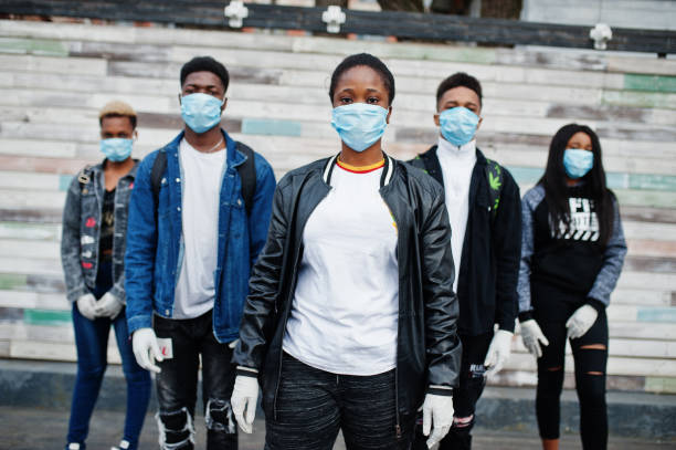 Group of african teenagers friends wearing medical masks protect from infections and diseases coronavirus virus quarantine. stock photo