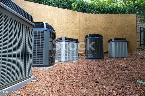 istock Group of air conditioner units next to building 1163077534