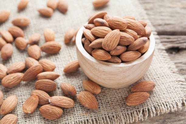 group of almonds  from wood bowl on wood background stock photo