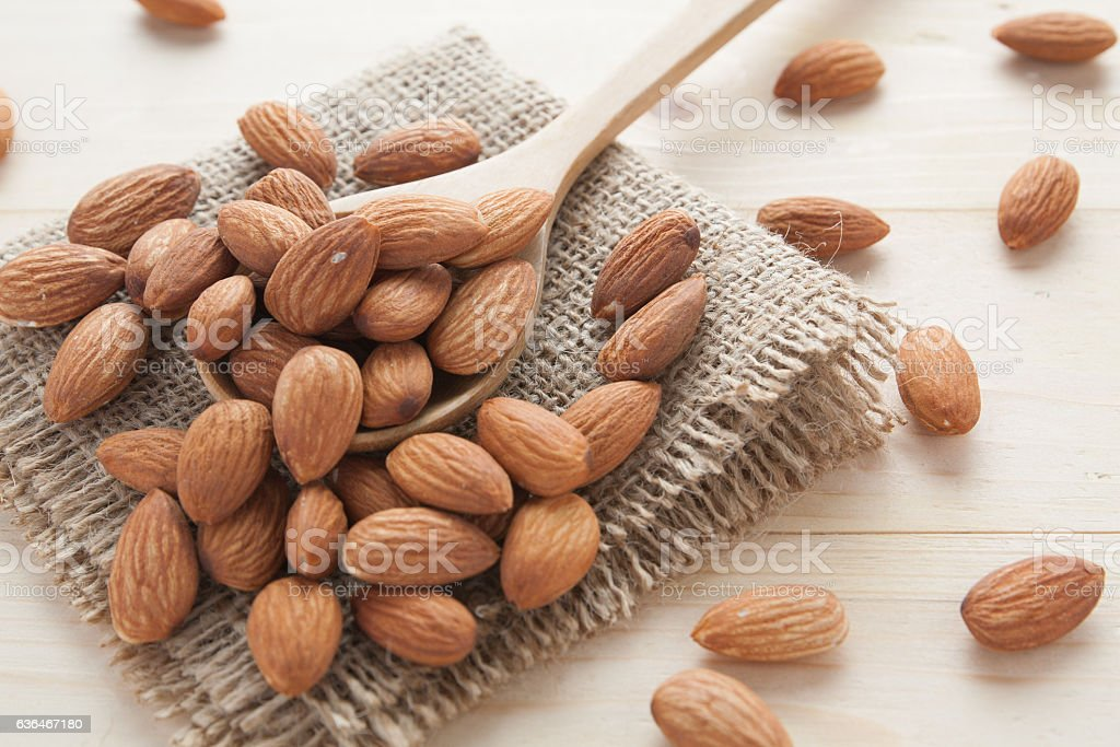 group of almonds  from wood spoon stock photo