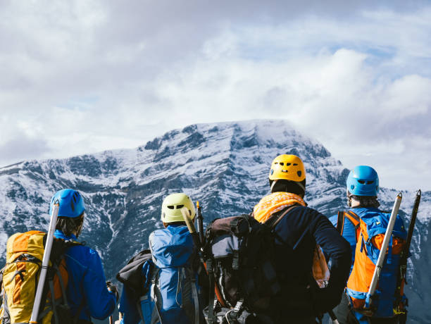 Group of  alpine climber team is watching the beautiful landscape  in the peak of mountain in winter stock photo