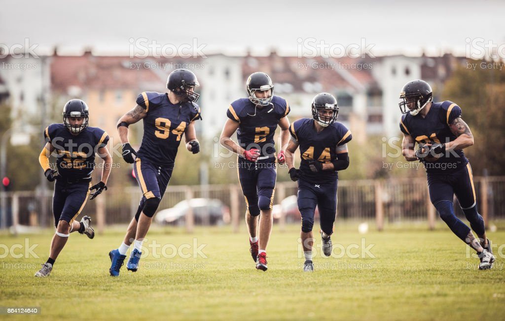 Group of American football players running on a field during the game. royalty-free stock photo