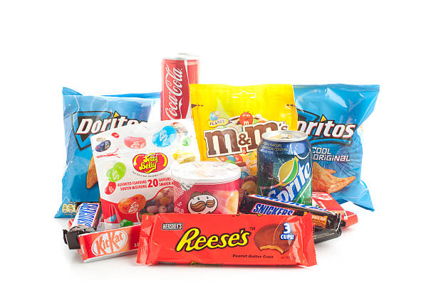 group of american junk food snack products on white background - kit kat stock photos and pictures